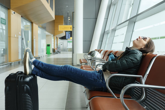 Bored and tired young woman is waiting her flight in airport sitting in hall. She sits and sleeping with her legs stretched out and puts them on the suitcase.