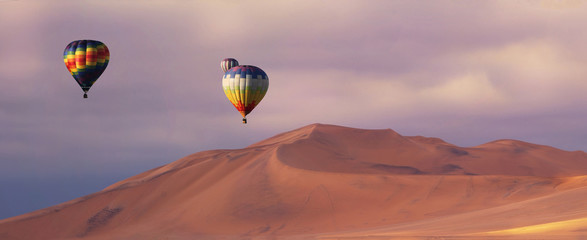 Three colorful hot air balloons over the sand dunes in Namib Desert. Artistic picture. Beauty world.