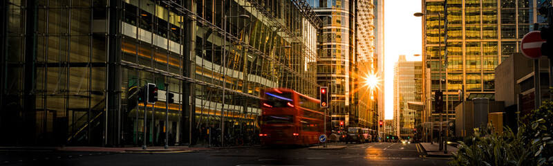 Busy London high street surrounded by large modern office buildings at sunset, England