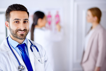 Arab doctor in the office with tablet and stethoscope, nurse working with patient on the background