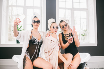 Picture showing group of happy friends in spa. girls with towels on heads having fun and taking selfie at home. Friendship, cosmetic, slumber party concept. Hen party with a bride in hotel