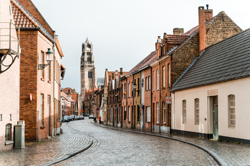 Ancient streets of the old city of Brugge in Belgium. An empty street from a lumber block extending into the distance in rainy weather.