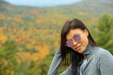 Outdoor portrait of glamour young brunette woman in sporty outfit and sunglasses posing at autumn park with beautiful foliage on the background.