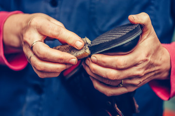 Hands of an experienced cobbler in the handmade footwear industry, finishing the soles of the shoes.