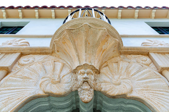 Sculpture of a face resembling a north-man viking man, on the top of an arched entrance door. Lincoln Road, Miami, Florida, USA