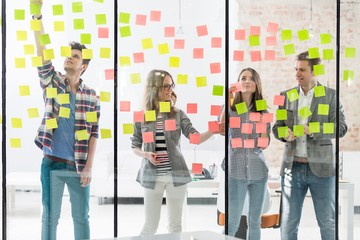 Creative business people discussing, organizing, analyzing plans through adhesive notes in office