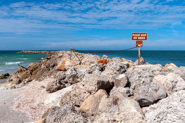 """""""Please Keep of the Rocks"""" sign, on a rock barrier wall at the north end of Bell Air Beach, Florida, USA"""