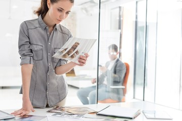 Businesswoman reading brochures in office against colleague in office