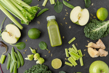 healthy eating, food and vegetarian diet concept - bottle of fresh green juice or smoothie, fruits and vegetables on slate stone background