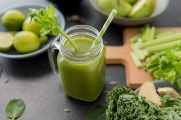 healthy eating, food and vegetarian diet concept - close up of glass mug of fresh green juice or smoothie with paper straw, fruits and vegetables on slate stone background