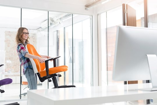 Businesswoman moving chair in new office