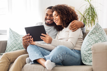 technology, internet and people concept - happy african american couple with tablet computer at home