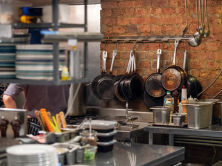 Smoked pans on a brick wall in a restaurant kitchen. The working environment of the restaurant. Kitchen tools.