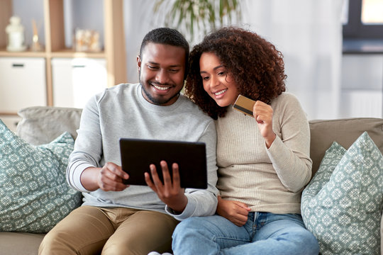 family, technology, online shopping and people concept - happy african american couple couple with tablet pc computer and credit card at home
