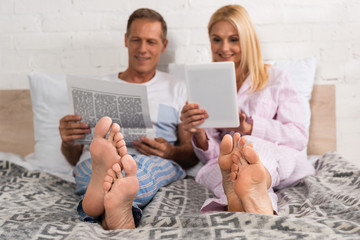 Man reading newspaper while wife using digital tablet on bed