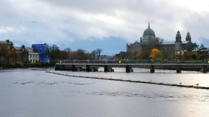 Wall Mural - Galway, Ireland. View of roman catholic cathedral of Galway, Ireland during the rainy day in autumn. River and cloudy sky, zoom out