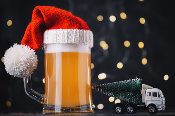 Christmas beer ale mug in Santa hat on dark background with bokeh garland. Craft beer