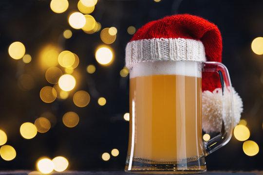 Christmas beer ale mug in Santa hat on dark background with bokeh garland. Craft beer