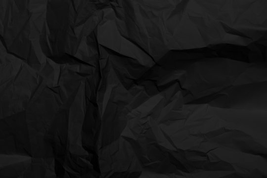 Black crumpled paper texture with folds, black background, wallpaper