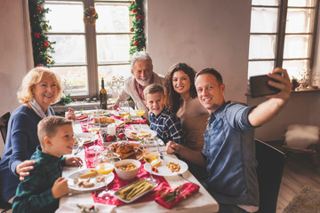 Family taking a selfe at Christmas dinner