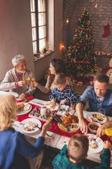 Family celebrating Christmas at home, having dinner