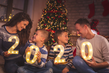 Parents and kids holding illuminative numbers 2020