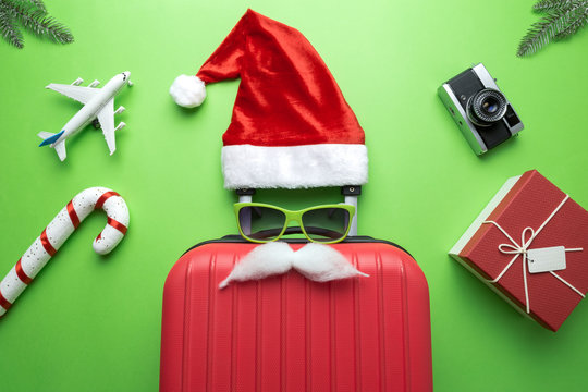Flat lay of Santa Claus luggage with travel and holiday accessories abstract on green.