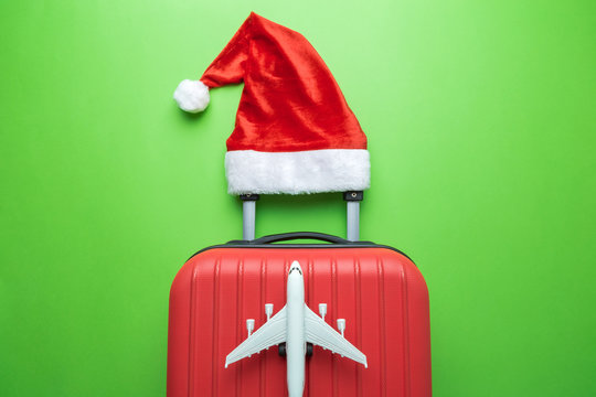 Suitcase with Santa hat and airplane model on green background minimal creative Christmas holiday travel concept.