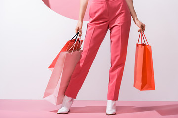 cropped view of woman holding shopping bags on pink and white