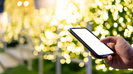 Male hand using smartphone in Xmas holiday and New Year celebration event. Mobile app for festive season concept. Blank white device screen.