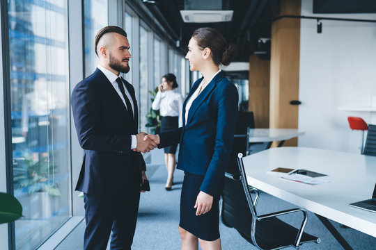 Friendly coworkers shaking hands after deal in office