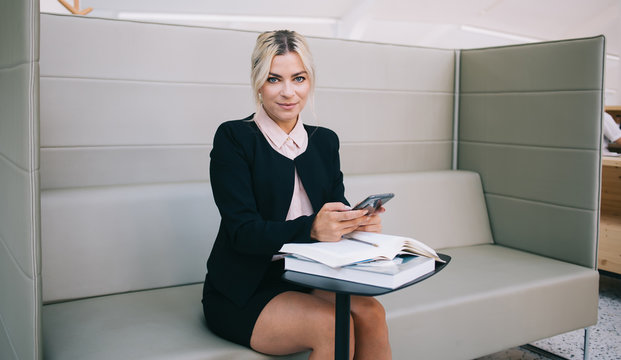 Portrait of successful female owner of small business looking at camera while waiting for meeting with partner in workspace, positive woman financial expert holding smartphone device sitting at table