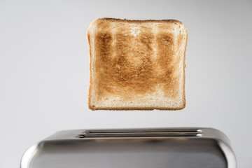 Roasted toast bread popping up of stainless steel retro toaster for breakfast preparation on a gray background.