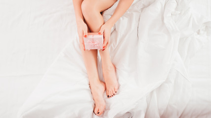 Birthday surprise. Cropped top view of woman with beautiful bare legs sitting on bed with pink gift box. Copy space.
