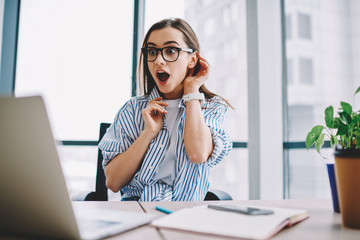 Emotional hipster girl surprised with getting victory in online contest reading news from laptop computer ,expressive young woman open mouth checking discounts for online shopping sitting at desktop .