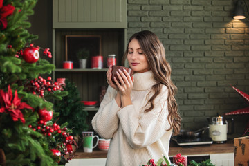 Beautiful happy young woman with smile on her face in kitchen in Christmas decorations