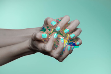 beautiful woman hands with holographic nail polish
