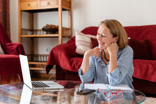 Middle age senior woman smilling while using computer