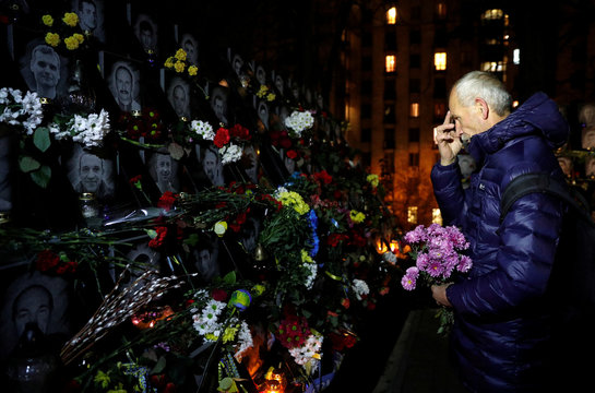 """A man takes part in a commemoration ceremony at a monument to the so-called """"Heavenly Hundred"""" to mark the sixth anniversary of the start of the anti-government uprising in Kiev"""
