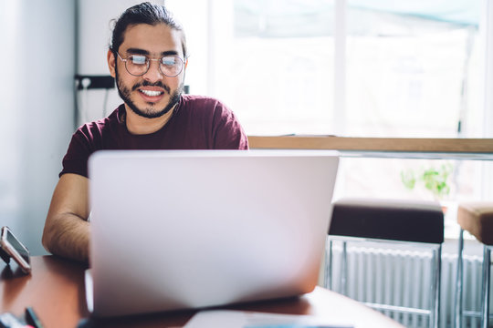 Smiling casual student using laptop