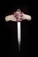Beautiful woman hands with glitter holding a sword close up can be used as background