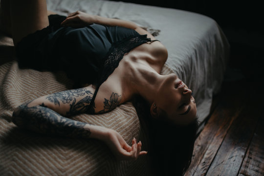 Young woman in black lingerie with tattoo on her arm lies on bed.