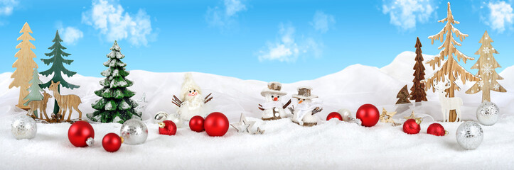 Bright winter Christmas fantasy arrangement with snow, wooden decoration, snowmen, baubles and blue sky