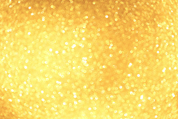 Golden sparkle glitters with bokeh effect and selectieve focus. Festive background with bright gold lights, champagne bubble. Christmas mood concept. Copy space, close up, texture, top view.
