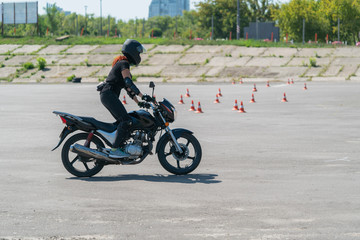 Girl learning to ride a bike at motordrome. Biker on a motorcycle.