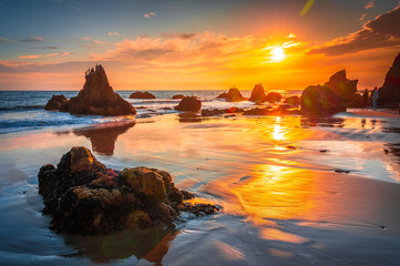 Beautiful and Colouful Orange Sunset beach of California with Rocks