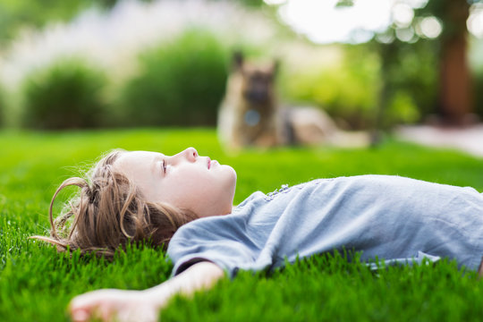 Side view of boy lying on green lawn looking up