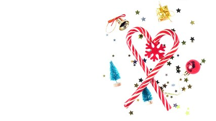 Heart shape made with candy canes on white background with new year decorations: toy trees. bell, snowflake, present, ball and confetti. Christmas mood.