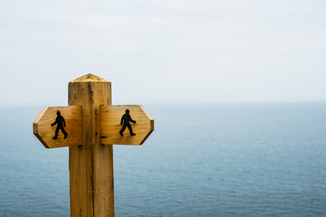 Close up of wooden signpost on hiking trail