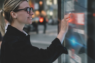 Smiling female standing at big display with advanced digital technology. Young woman touching with finger sensitive screen of interactive kiosk for find information while standing on street in evening Wall mural